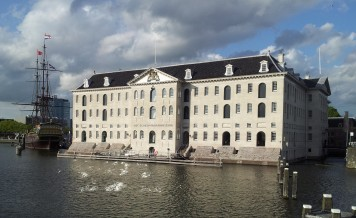 I don't know what this is, but it's a beautiful building sitting on the water with an old ship next to it. I like it.